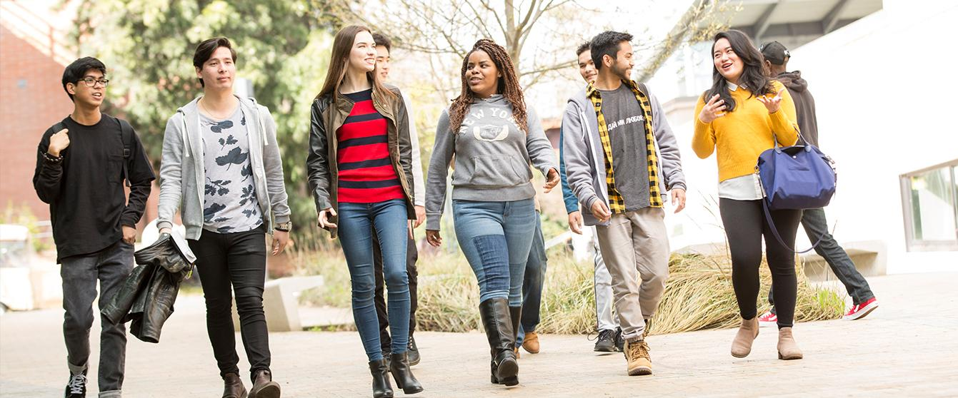 An image of students walking toward the camera, talking.