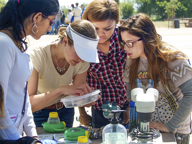 Students with a teacher looking at science sample