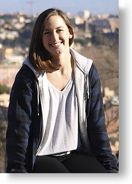 Katelynn Cunningham, young woman smiling, sitting on a ledge in Italy
