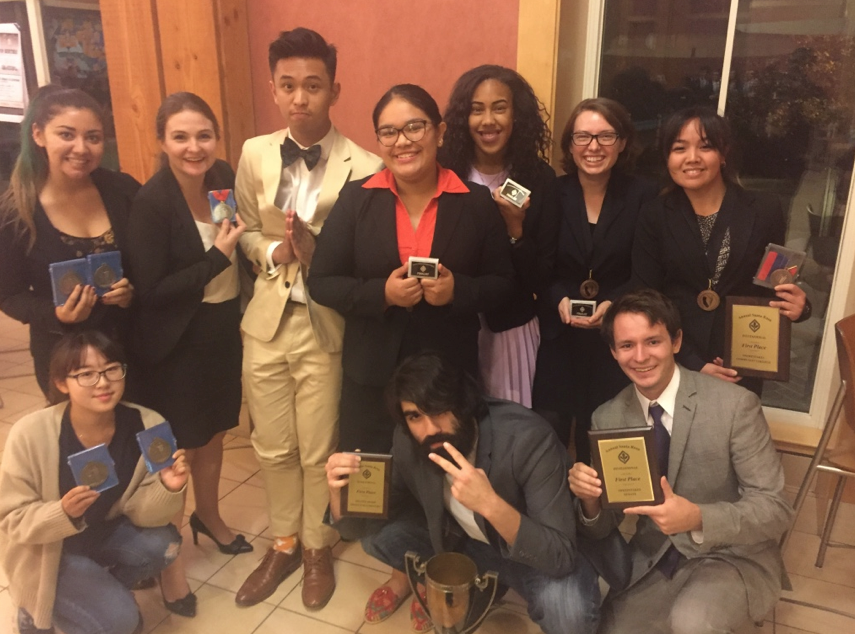 dvc 2017 speech and debate team. Students smilling, standing, holding awards and trophy.
